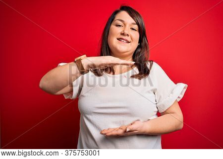 Beautiful brunette plus size woman wearing casual t-shirt over isolated red background gesturing with hands showing big and large size sign, measure symbol. Smiling looking at the camera. Measuring