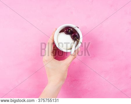 Frozen Yogurt Dessert In Cup With Cherries. Female Hand Holding Fresh Gelato On Pink Background. Fla