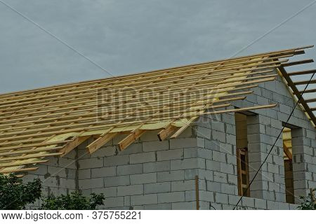 Part Of An Unfinished White Brick House With A Roof With Boards And Wooden Brown Formwork Against A