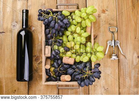 Box With Grapes, A Bottle Of Wine, A Corkscrew, On A Wooden Background. View From Above. Winemaking
