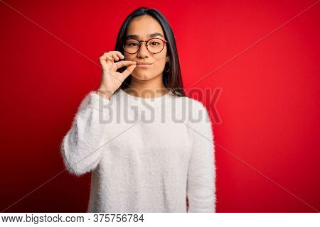 Young beautiful asian woman wearing casual sweater and glasses over red background mouth and lips shut as zip with fingers. Secret and silent, taboo talking