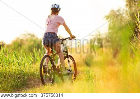 Mood. Joyful Young Woman Riding A Bicycle At The Riverside And Meadow Promenade. Inspired By Surroun