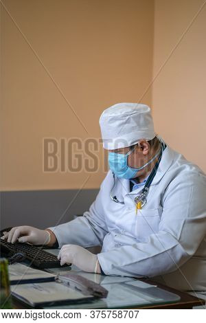 Masked Gp Doctor Using Computer. General Practitioner Works With Computer Application Sitting At Des