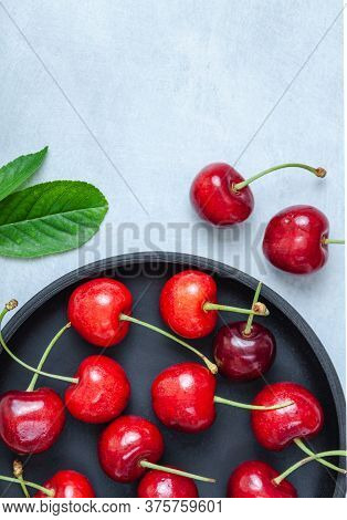 Cherry With Leaf On Plate And Water Dropsand On Grey Stone Table. Ripe Ripe Cherries. Sweet Red Cher