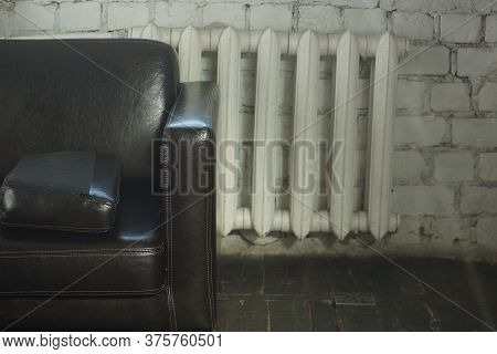 A Large Brown Leather Sofa Stands In A Room With A White Brick Wall Near The Radiator