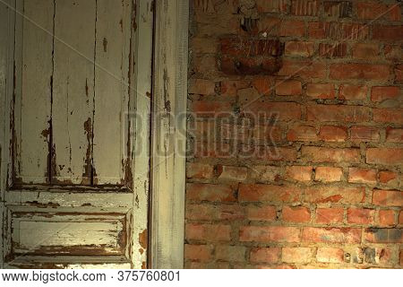 Old, White Painted Doors, Closed, Indoors With Red Brick Walls, Illuminated By The Rays Of The Sun F