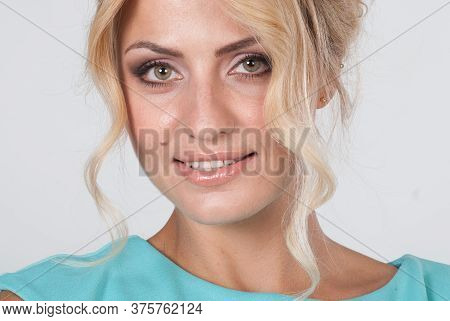 Closeup Portrait Of A Young Beautiful Woman In A Light Blue Dress In The Studio