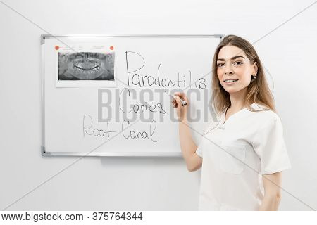 Young Female Dentist Doctor Standing In Front Of A White Board Examines An X-ray Picture Or Writes S