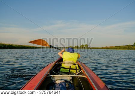 A Little Boy Kayaks On The River In The Summer And Rowing An Oar.