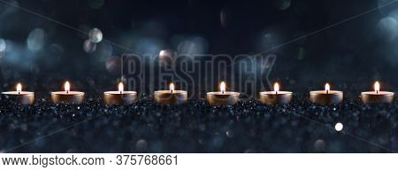 Candlelights In The Darkness With Blurred Golden Bokeh. Horizontal Background With Short Depth Of Fi