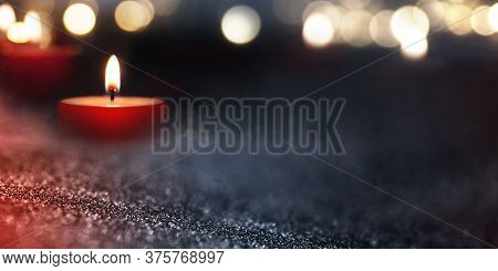 Candlelight In The Darkness With Blurred Golden Bokeh. Background With Short Depth Of Field For Reli