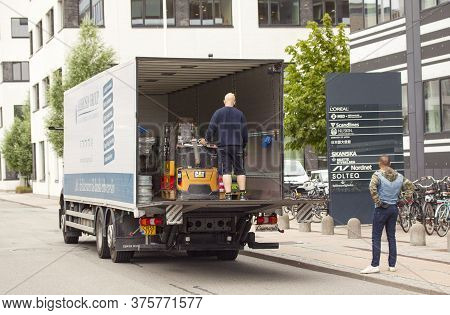 Delivery Man Unloaded Truck With A Forklift On A Tailgate Loader Of A Delivery Truck In Front Of An