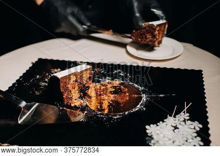 Amazing Cakes. A Black-gloved Chef Is Slicing A Chocolate Wedding Cake. The Wedding Cake Is Deliciou
