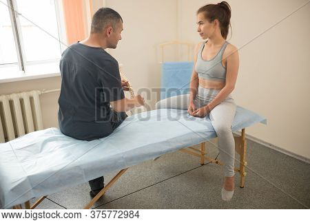 Woman Having A Talking With Osteopathic Doctor In The Clinic