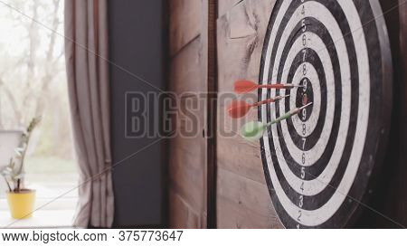 Three Darts Arrows Hit The Bullseye. Dart Board Hanging On A Wooden Wall Of Home Or Office. Hit Goal