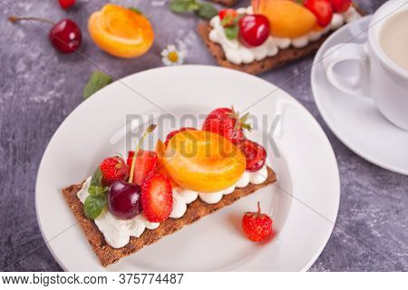 Crisp Fitness Health Bread With Creme Cheese, Fruit And Berries And Cup Of Tea On The White Plate On