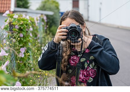 A Young Preteen Girl Takes Photos With A Dslr Camera. The Camera Covers Her Face. Blurry, Soft Backg