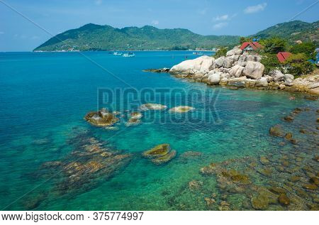 Tropical island vacation, Coast of Koh Tao island with turquoise clear sea water, rocky bottom, houses with red roof behind granite boulders. Popular destination for travel holidays in Thailand
