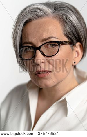 Smart Mature Woman In White Shirt Looking Thoughtfully At The Camera. Pretty Caucasian Gray Haired M