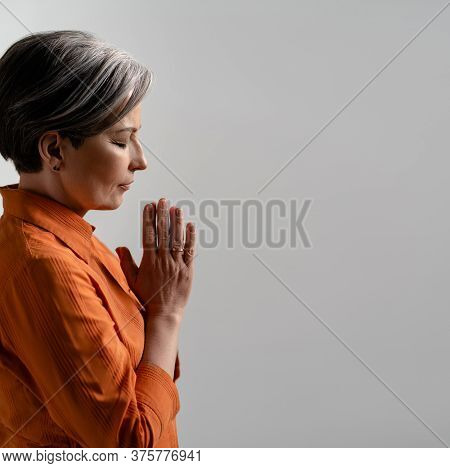 Spiritual Caucasian Woman Prays With Her Hands Clasped. Side View Of Meditating Mature Woman With Cl