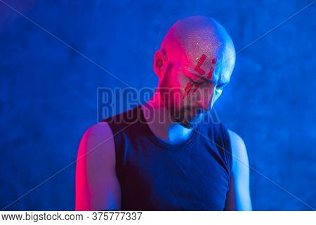 Portrait Of Stylish Bald Man With Drawing On Face. Fluorescent Paint In Ultraviolet And Neon Light,