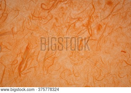 background of amber and orange backlit, handmade, mulberry paper