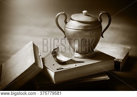 On A Pile Of Old Battered Books About Magic Is An Old Lamp With A Genie Who Grants Wishes, And Next