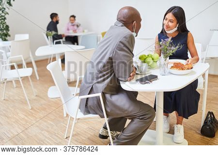 Multicultural businesspeople as a couple flirting in the cafeteria with a face mask on their chin