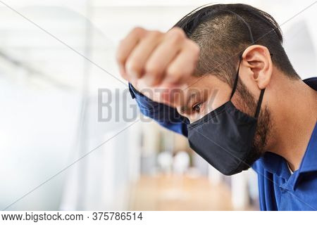 Businessman with face mask for Covid-19 and coronavirus suffers from burnout due to overload
