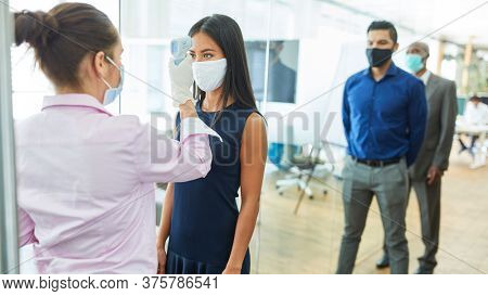 Businesswoman having contactless fever on forehead at colleague with face mask because of Covid-19
