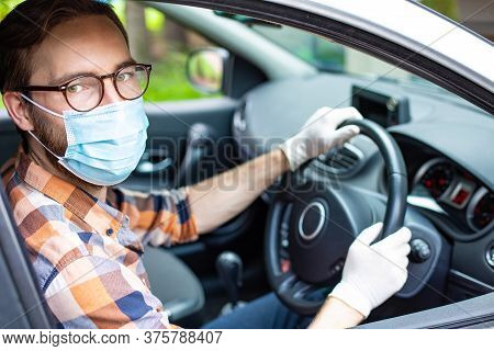 Car Driver With Protective Gloves And A Face Mask In A Right-hand Drive Vehicle Everyday Prevention
