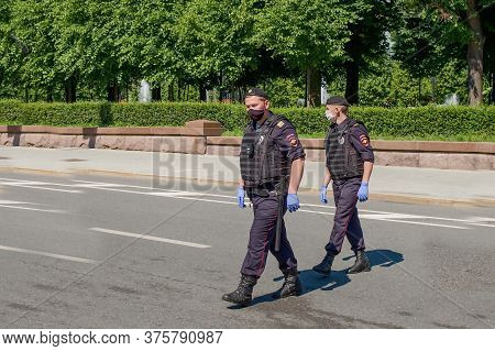 Two Armed Bodyguards In Black Uniforms, Protective Masks, Gloves Patrol City Streets During Global P