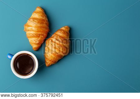 Horizontal Copy Space With Two Croissants And Cup Of Fresh Fragrant Coffee At Blue Background. Conce
