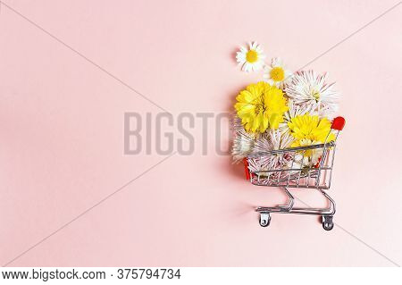 Shopping Trolley With Flowers And Copy Space On Pink Background. Festive Shopping And Sale.