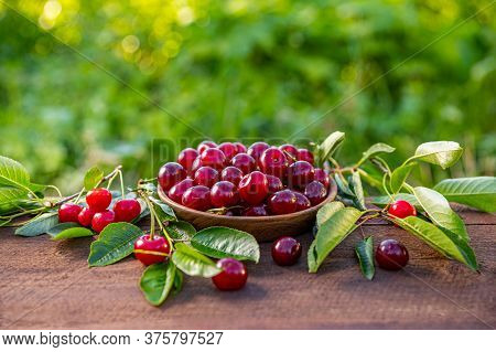 Cherries In A Wooden Bowl On A Wooden Table, Outdoor Shot