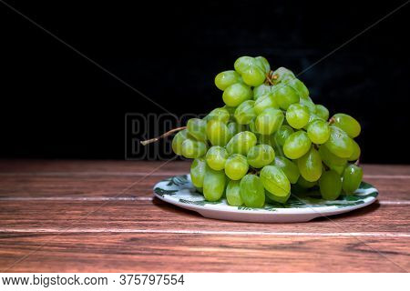 Green Seedless Grapes In A White Bowl On A Wooden Board