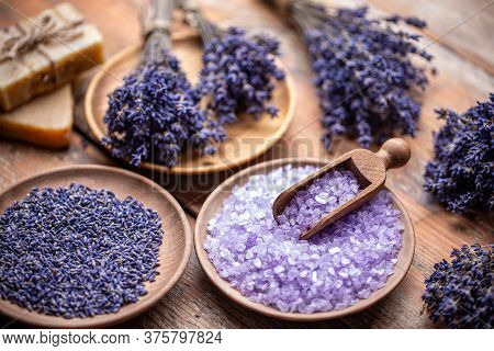 Lavender Flowers And Coloured Bathing Salt In Wooden Plate