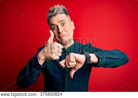 Young handsome modern man wearing elegant green shirt over red isolated background Doing thumbs up and down, disagreement and agreement expression. Crazy conflict