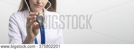 Close Up Portrait Of Unrecognizable Caucasian Doctor Woman With Stethoscope Holding Using In Directi