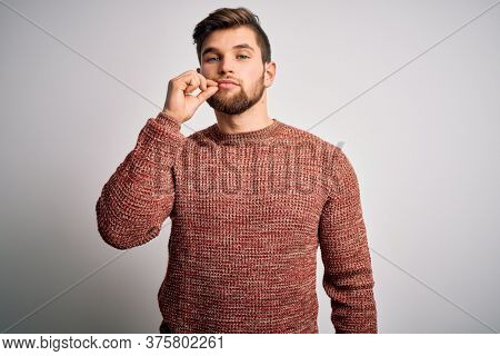 Young blond man with beard and blue eyes wearing casual sweater over white background mouth and lips shut as zip with fingers. Secret and silent, taboo talking