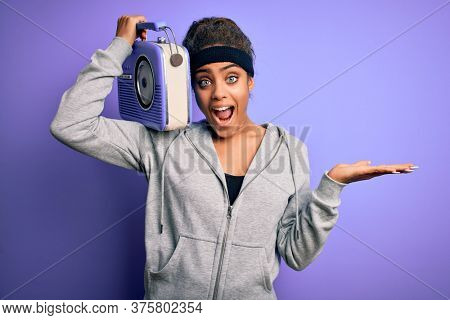 Young african american afro girl listening to music holding vintage radio over purple background very happy and excited, winner expression celebrating victory screaming with big smile and raised hands