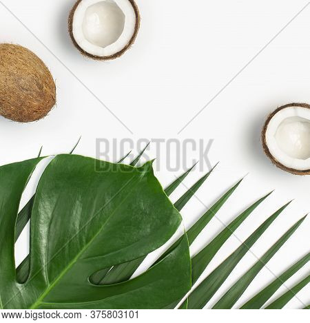 Tropical Leaves And Fresh Coconut On White Background. Flat Lay, Top View, Copy Space. Summer Backgr