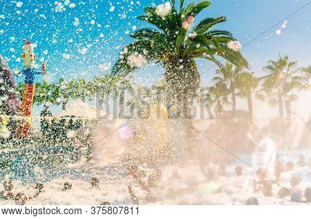Foam Pool Party, Bubbles Blower And Crowded Pool With People Swimmng, Dancing Relaxing And Having Fu