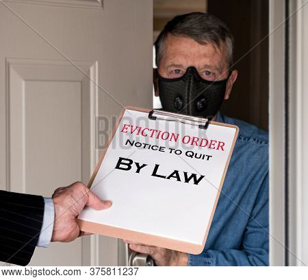 Open Front Door With Man In Suit Handing An Eviction Notice To A Defaulting Renter With Face Mask Du