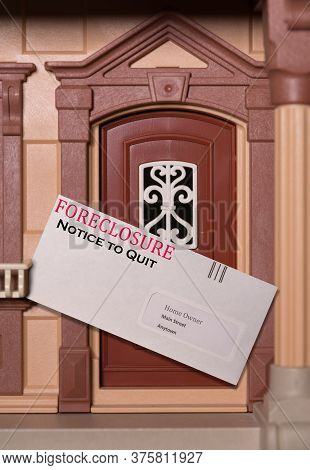 Envelope Being Served At Toy Dollhouse Containing A Foreclosure Notice Due To Failure To Pay Rent On