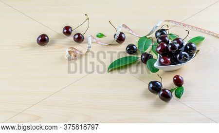 Dosing Tape And Ripe Fresh Cherries On The Wooden Table. Healthy Eating, Balanced Fruit Diet Concept