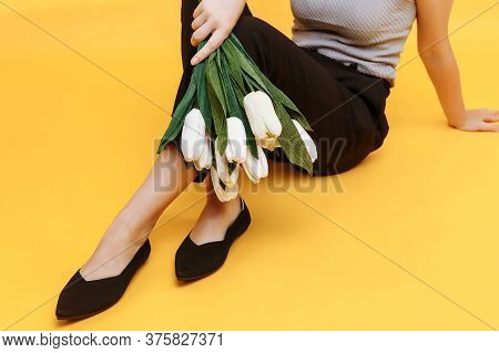 Beautiful Female Legs Are Dressed In Stylish Black Flat Shoes. Black Sandals On A Yellow Background