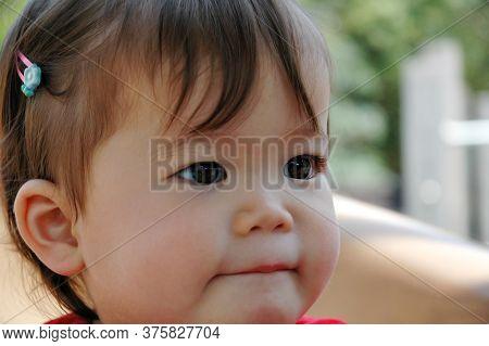 Close-up Of Beautiful Baby Asian Girl Sucking Her Bottom Lip.