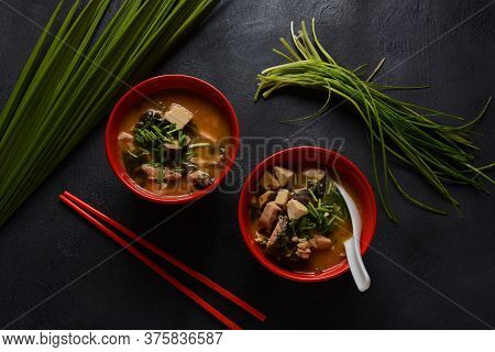 Japanese Miso Soup In Two Red Japanese Bowls On The Black Table. Miso Soup With Tofu, Tuna, Herbs An