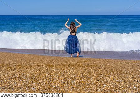 Beautiful Girl Staying Near The Wavy Sea. Landscape Blue Background. Outdoor Landscape. Beautiful Mo